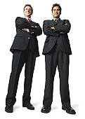 low angle of two business men in suits as they fold their arms and smile