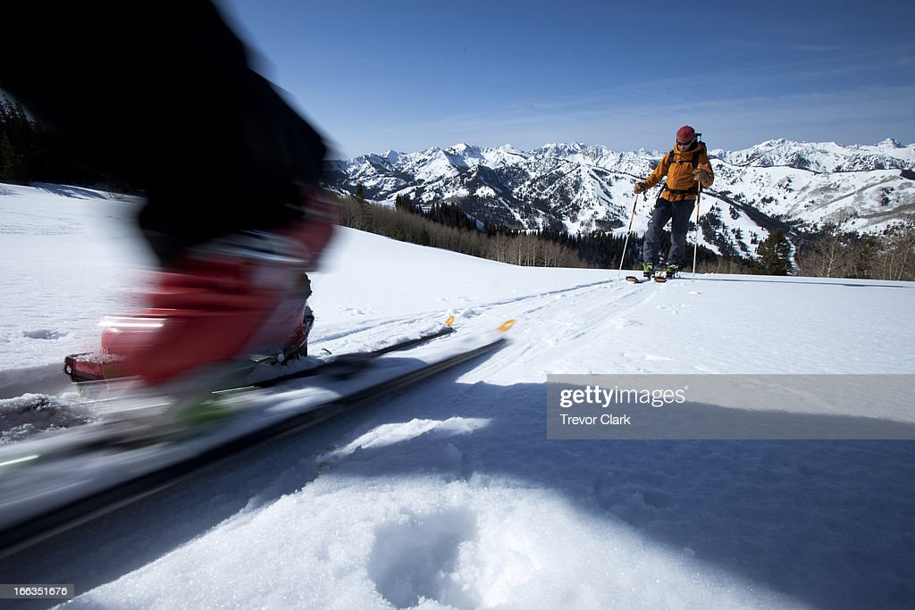 Low angle perspective of a skier's boot motion blurred with a skier int he background.