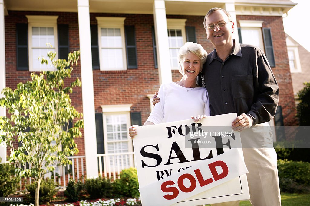 Low angle portrait of a mature couple standing in front of their recently sold home