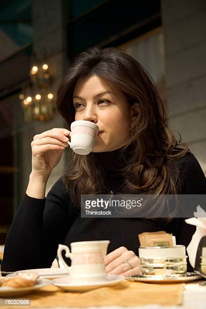Low angle portrait of a woman sitting at a cafe table drinking her cup of espresso.