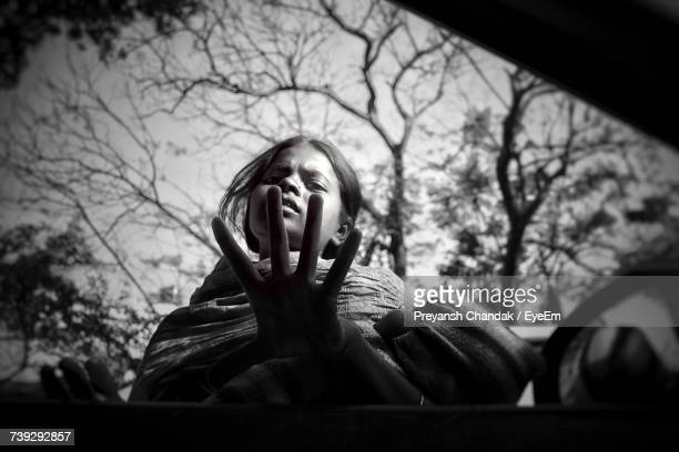 Low Angle Portrait Of Female Beggar Gesturing Seen Through Car Window