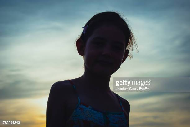 Low Angle Portrait Of Girl Against Sky During Sunset