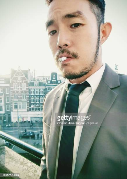 Low Angle Portrait Of Handsome Businessman Smoking Cigarette
