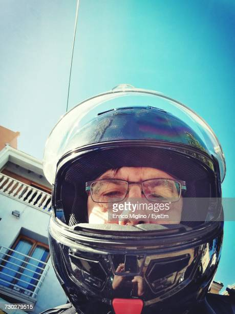 Low Angle Portrait Of Man Wearing Helmet Against Blue Sky