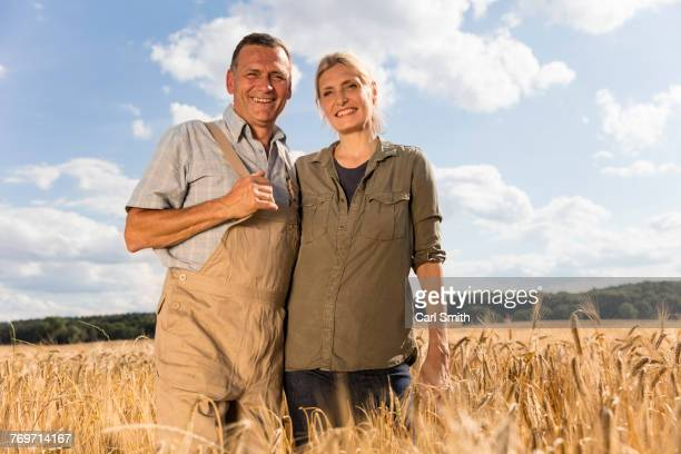 Low angle portrait of smiling mature couple standing at farm against sky