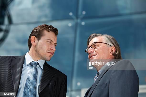 Low Angle-Porträt von zwei Geschäftsleute und Corporate-Gebäude im Hintergrund