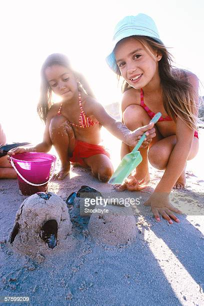low angle portrait of two young girls (4-8) playing on the beach with a spade and a bucket
