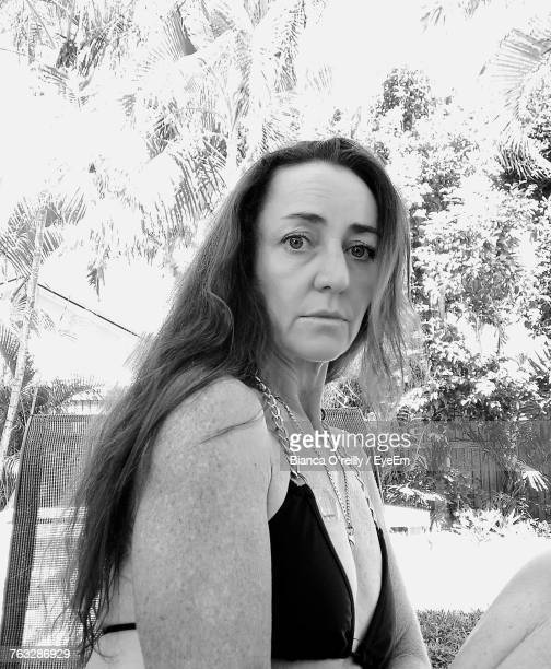 Low Angle Portrait Of Woman Sitting At Park
