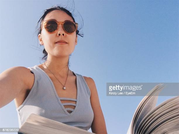 Low Angle Portrait Of Young Woman Holding Book Against Clear Blue Sky