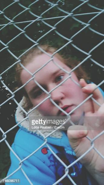 Low Angle Portrait Of Young Woman Seen Through Chainlink Fence