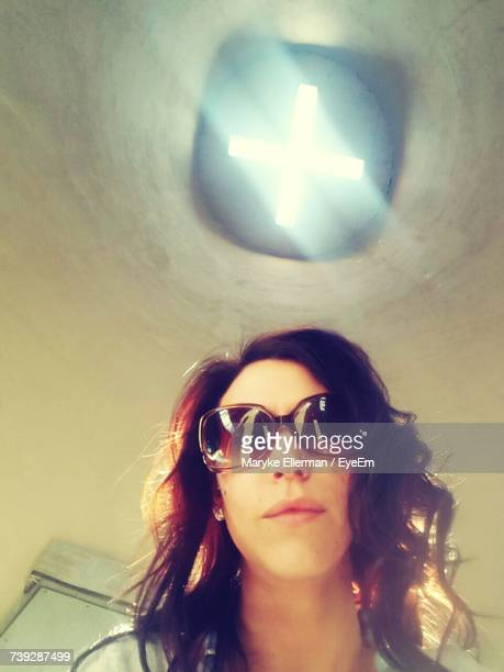 Low Angle Portrait Of Young Woman Wearing Sunglasses Against Skylight