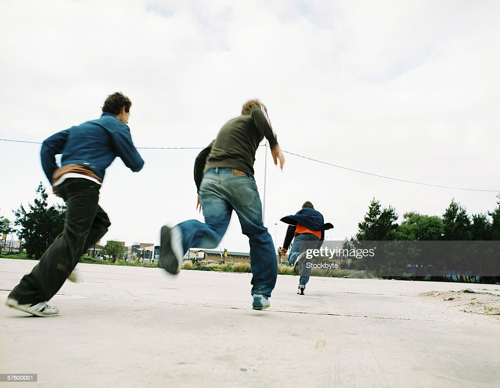 Low angle rear view of three young men running : Stock Photo