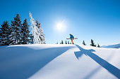 Low angle shot of a male skier walking on top of the mountain with his skis on a sunny winter day sunlight nature recreation skiing resort lifestyle sportive concept