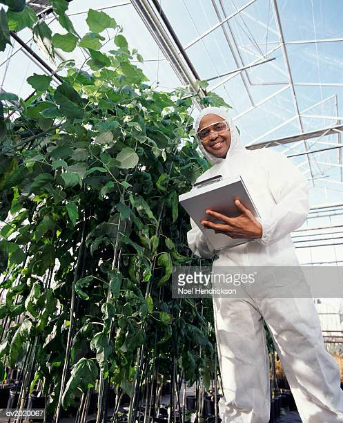 Low Angle Shot of a Scientist Wearing a Clean Suit and Holding a Clipboard, in a Greenhouse