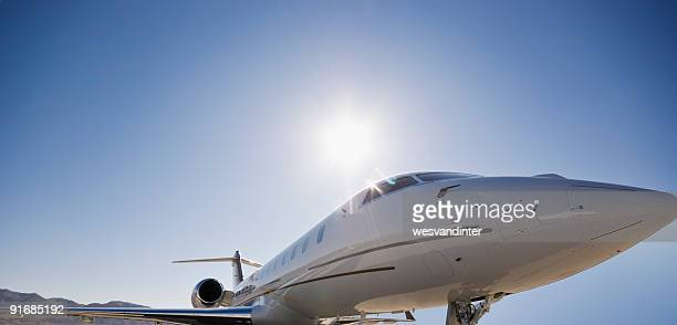 Low angle shot of personal jet with background hills and sun