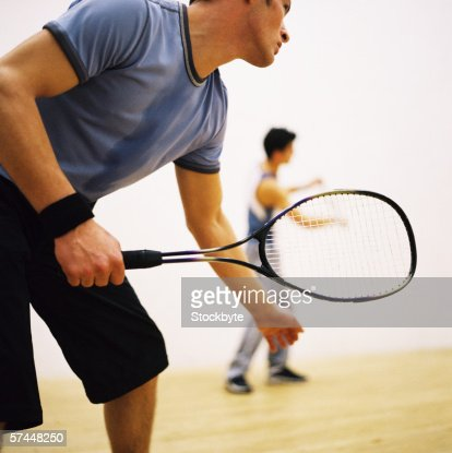 low angle side view of a man playing tennis outdoors