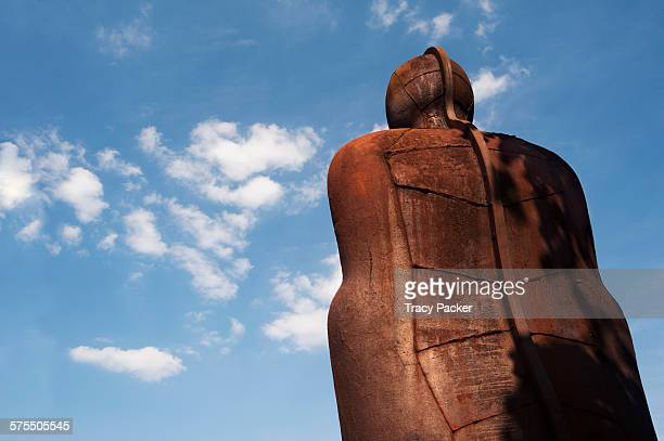 A low angle view looking up at the back of the iconic 'Iron Man' sculpture a 6 metre tall leaning tilting iron figure made by the artist Antony...