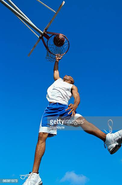 low angle view of a basketball player dunking a basketball