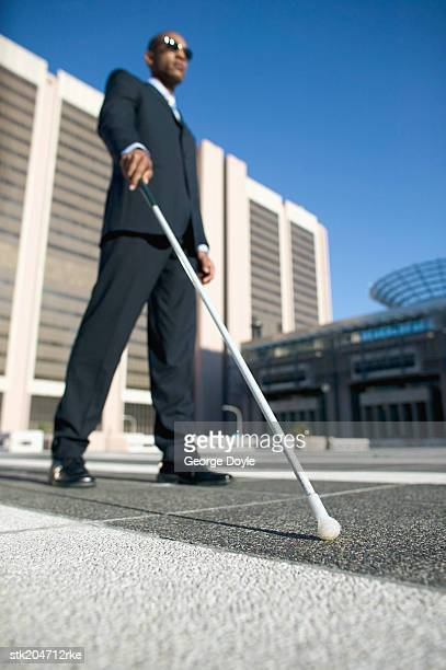 low angle view of a blind man walking with the aid of a white stick