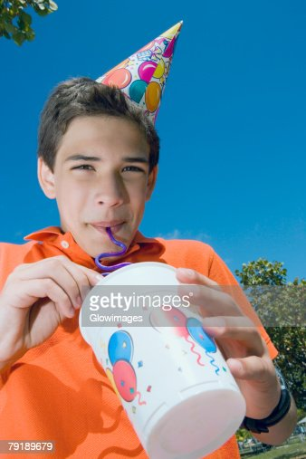 Low angle view of a boy drinking with a drinking straw : Foto de stock