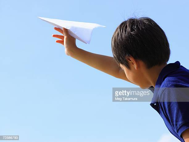 Low angle view of a boy holding a paper airplane
