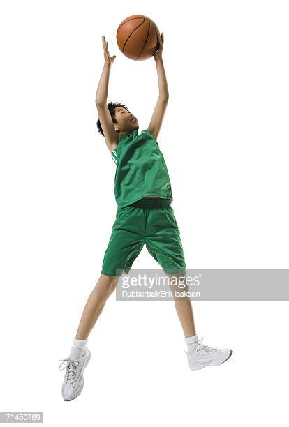 Low angle view of a boy jumping and throwing a basketball