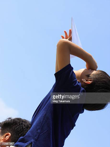 Low angle view of a boy sitting on his father's shoulders flying a paper airplane