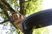 Low angle view of a boy swinging on a tire swing