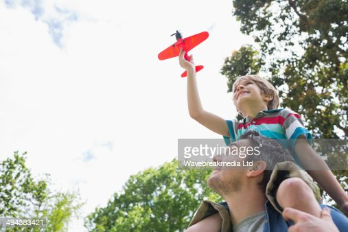 Boy with toy aeroplane sitting on father's shoulders : Stock Photo