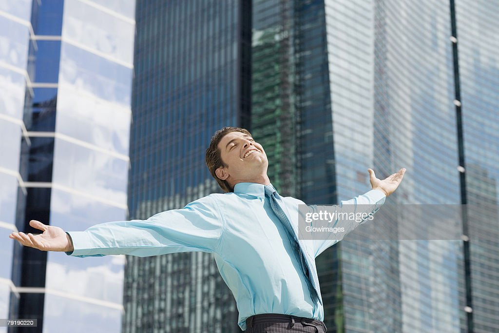 Low angle view of a businessman standing with his arms outstretched : Stock Photo