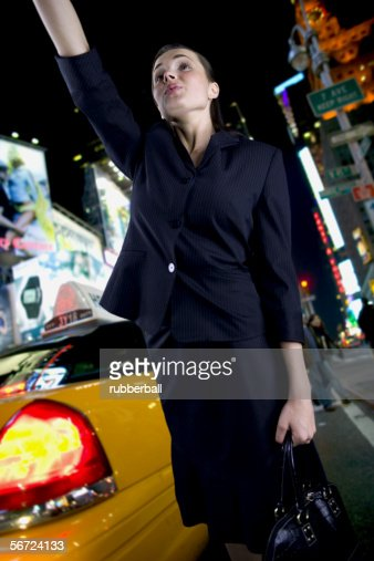 Low angle view of a businesswoman hailing a taxi