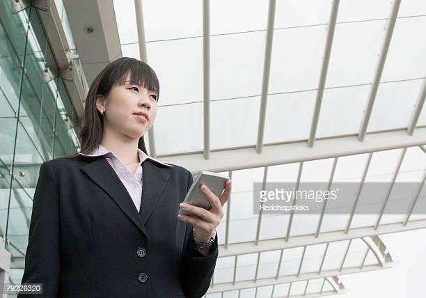 Low angle view of a businesswoman holding a personal data assistant and waiting at an airport lounge