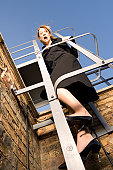 Low angle view of a businesswoman standing on a ladder and looking scared