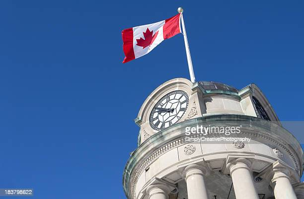 Low angle view of a Canadian flag flying on a clock tower
