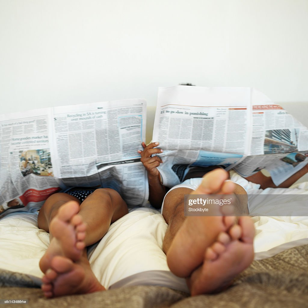 low angle view of a couple reading newspapers while lying in bed : Stock Photo