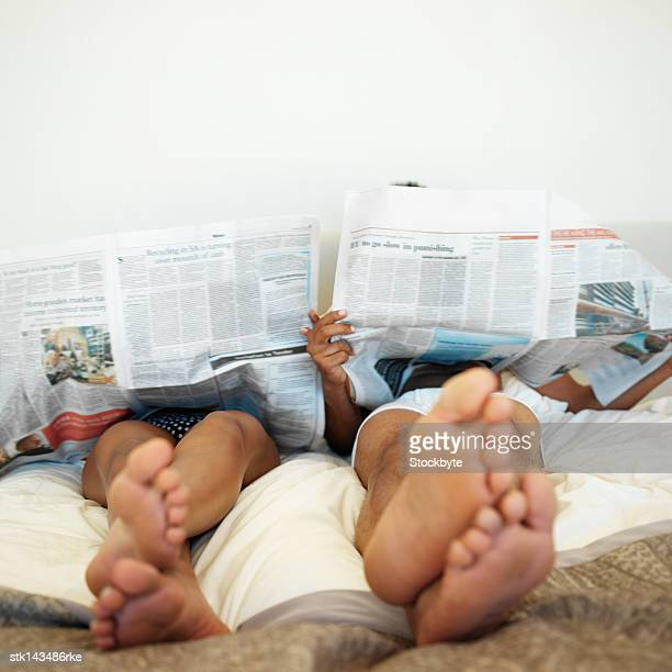 low angle view of a couple reading newspapers while lying in bed
