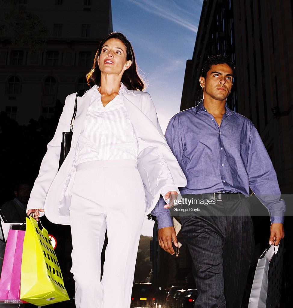 low angle view of a couple walking on a street with shopping bags : Stock Photo