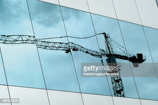 Low angle view of a crane reflected on the window : Stock-Foto