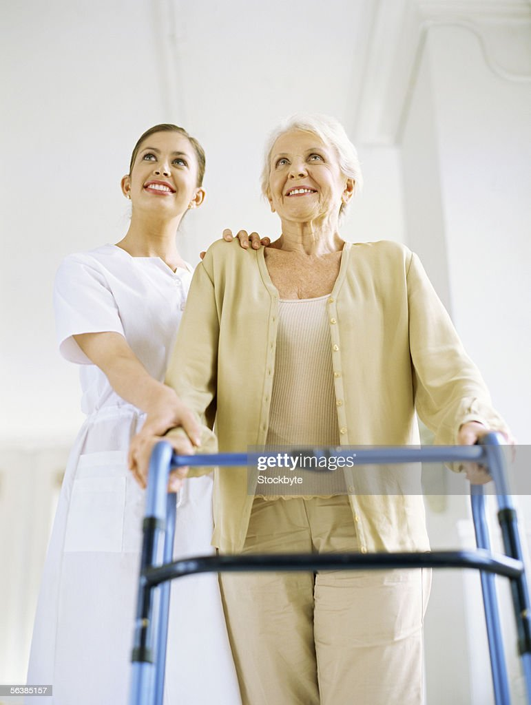low angle view of a female nurse helping a patient to walk with a walker : Stock Photo