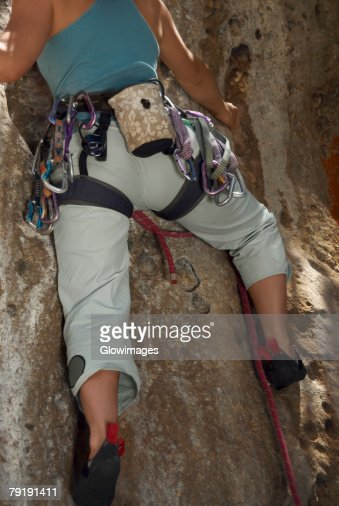 Low angle view of a female rock climber climbing a rock : Stock Photo