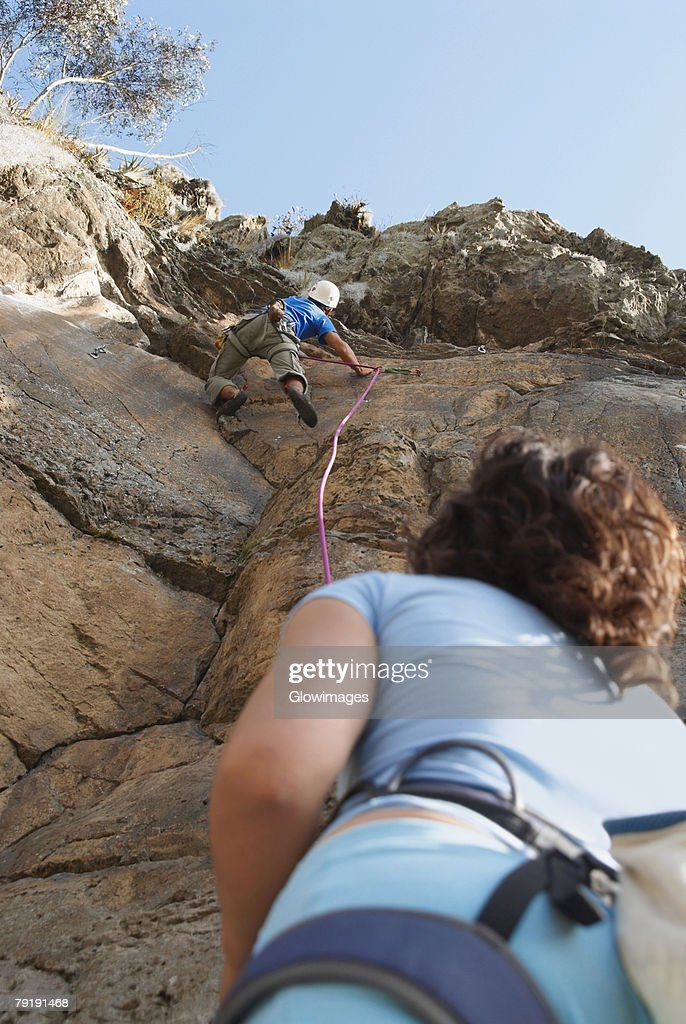 Low angle view of a female rock climber looking at a male rock climber scaling a rock face : Foto de stock