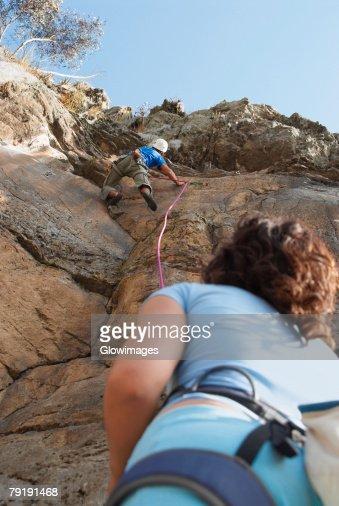 Low angle view of a female rock climber looking at a male rock climber scaling a rock face : Foto de stock