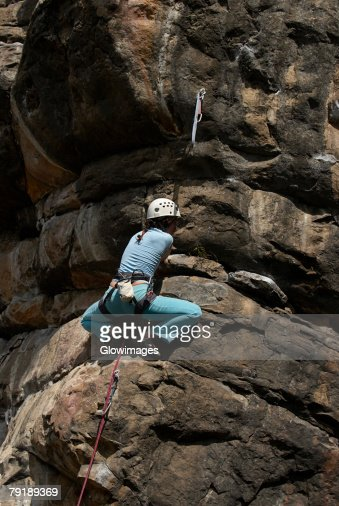 Low angle view of a female rock climber scaling a rock face : Foto de stock