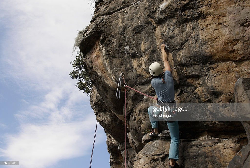 Low angle view of a female rock climber scaling a rock face : Stock Photo