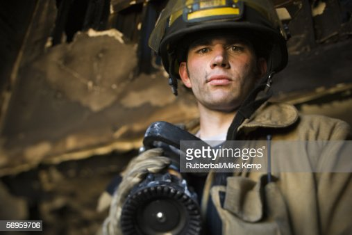 Low angle view of a firefighter holding a fire hose