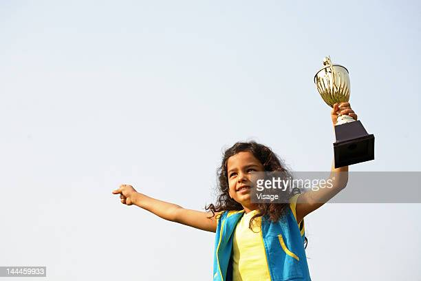 Low angle view of a girl holding up a trophy