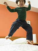 Low angle view of a girl jumping on a bed