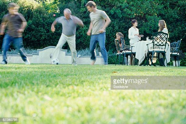 Low angle view of a grandson playing football his grandfather and father