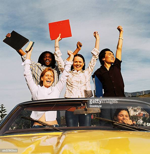 low angle view of a group of young men and women standing in a convertible car with arms raised in celebration