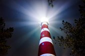 Low angle view of a lit lighthouse against sky